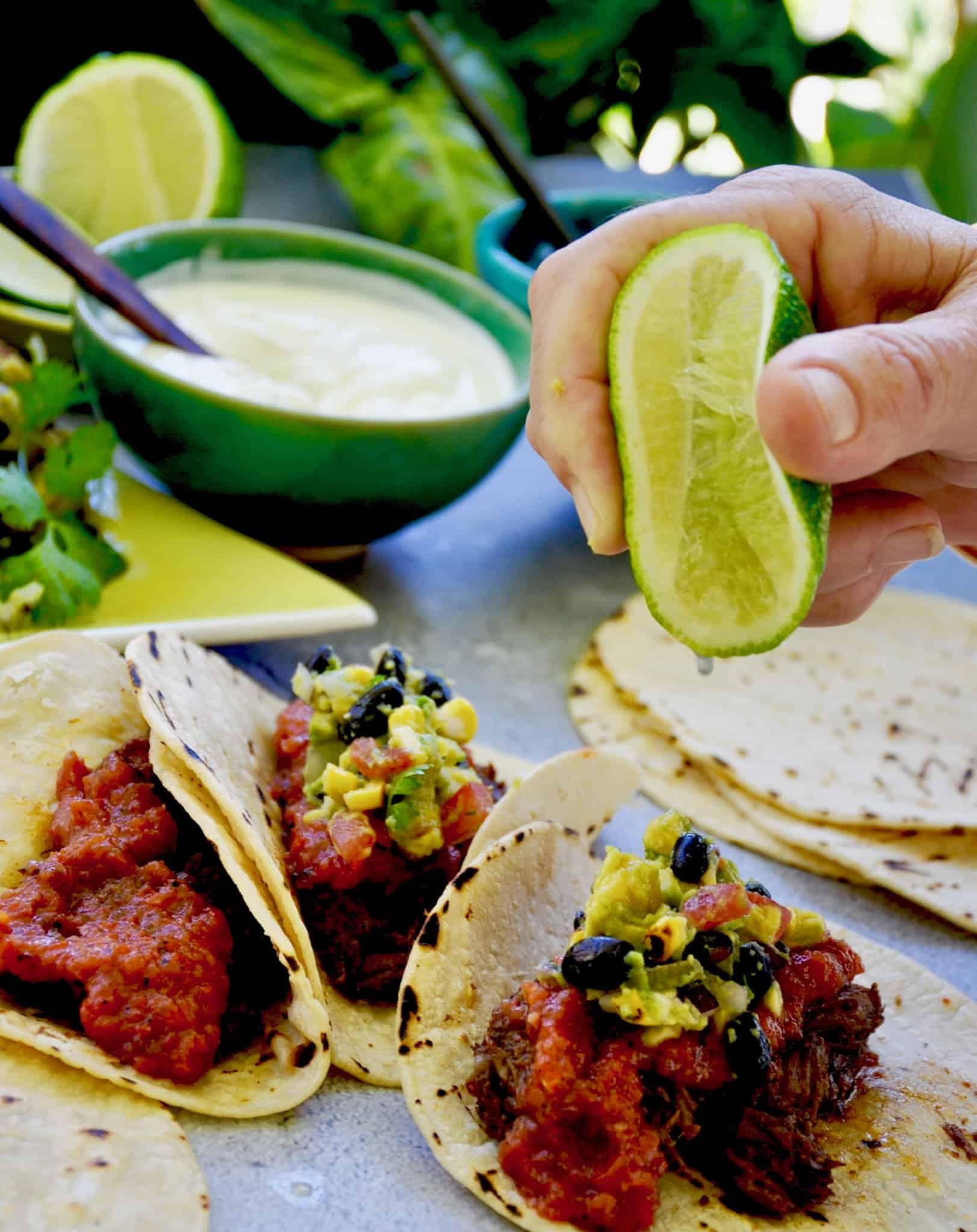 smoky red salsa on a taco with salsa and a lime half being squeezed over the taco