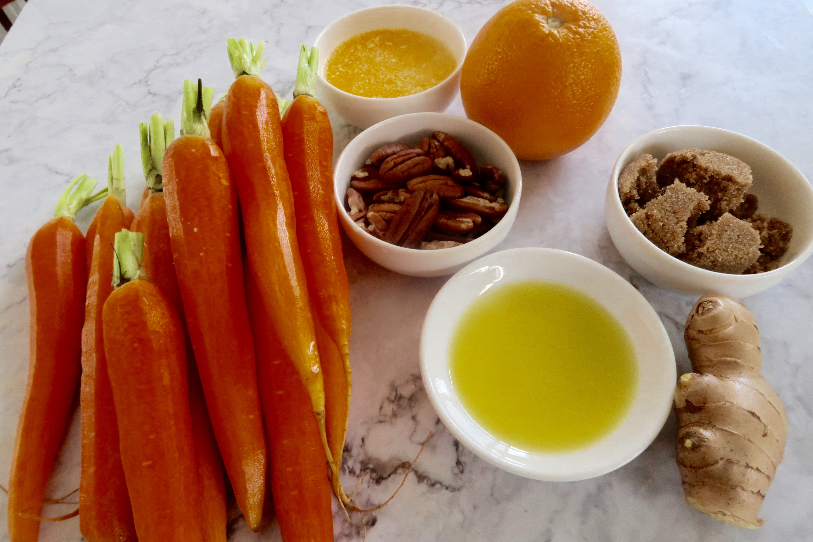 brown sugar and ginger glazed carrots ingredients laid out on a marble bench