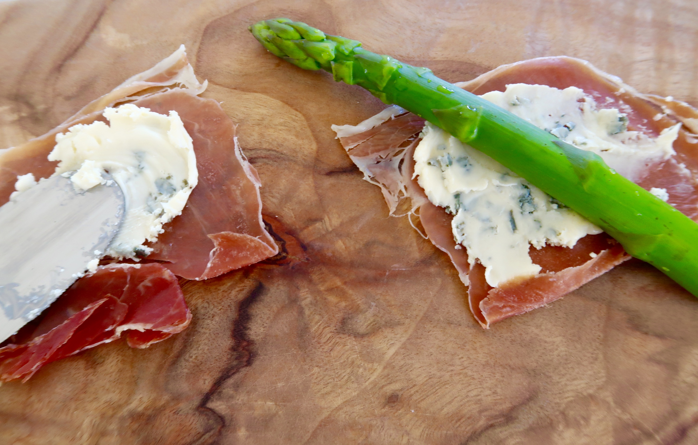 asparagus with prosciutto and blue cheese preparing on a wooden chopping board