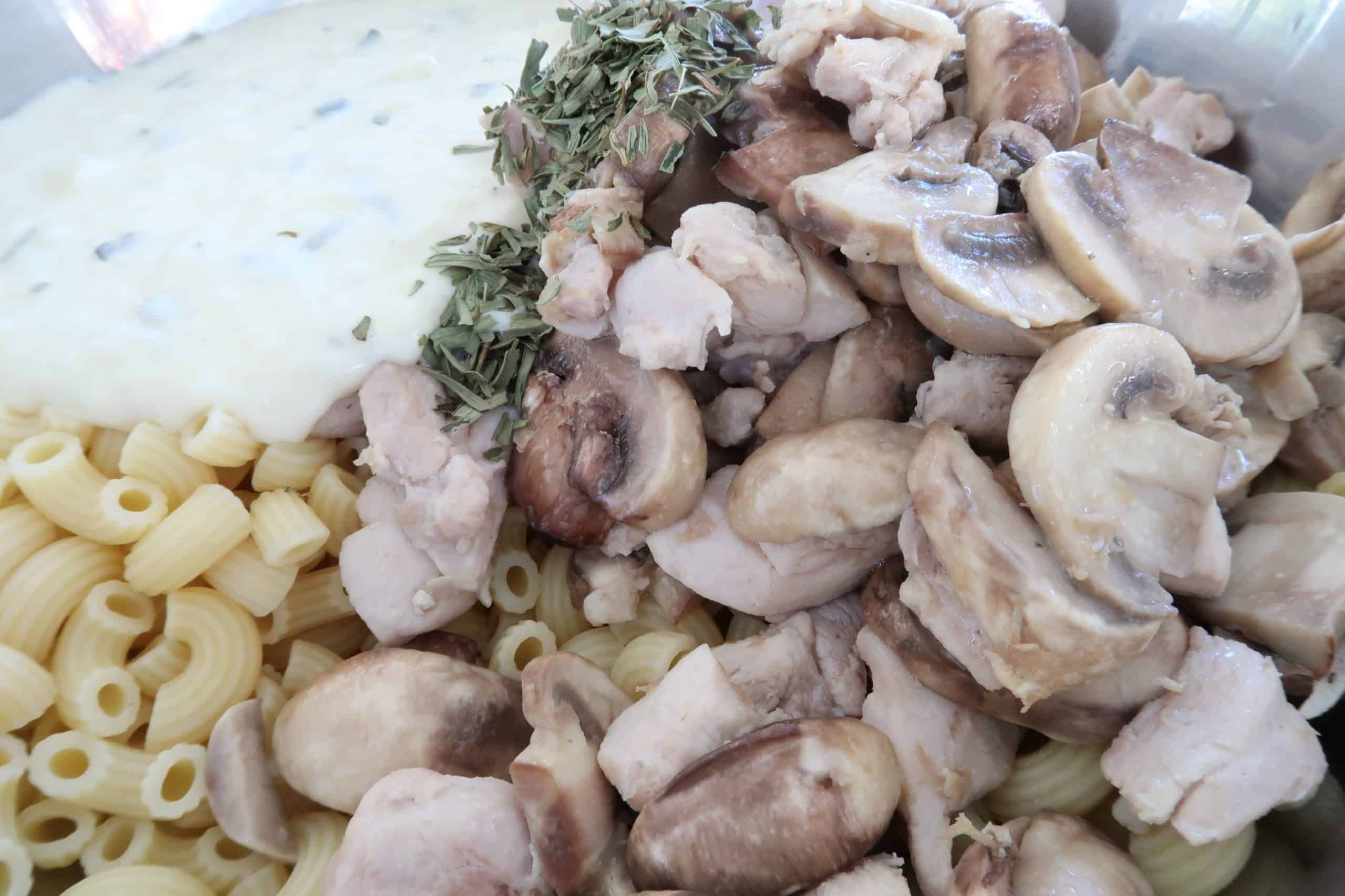 chicken and mushroom pasta bake ingredients in a bowl about to be mixed