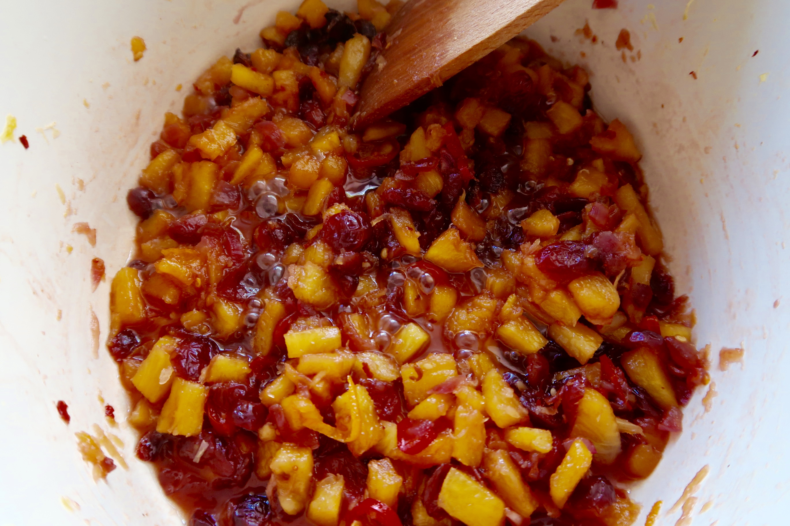 spicy pineapple and cranberry relish simmering on the stove with a wooden spoon for stirring