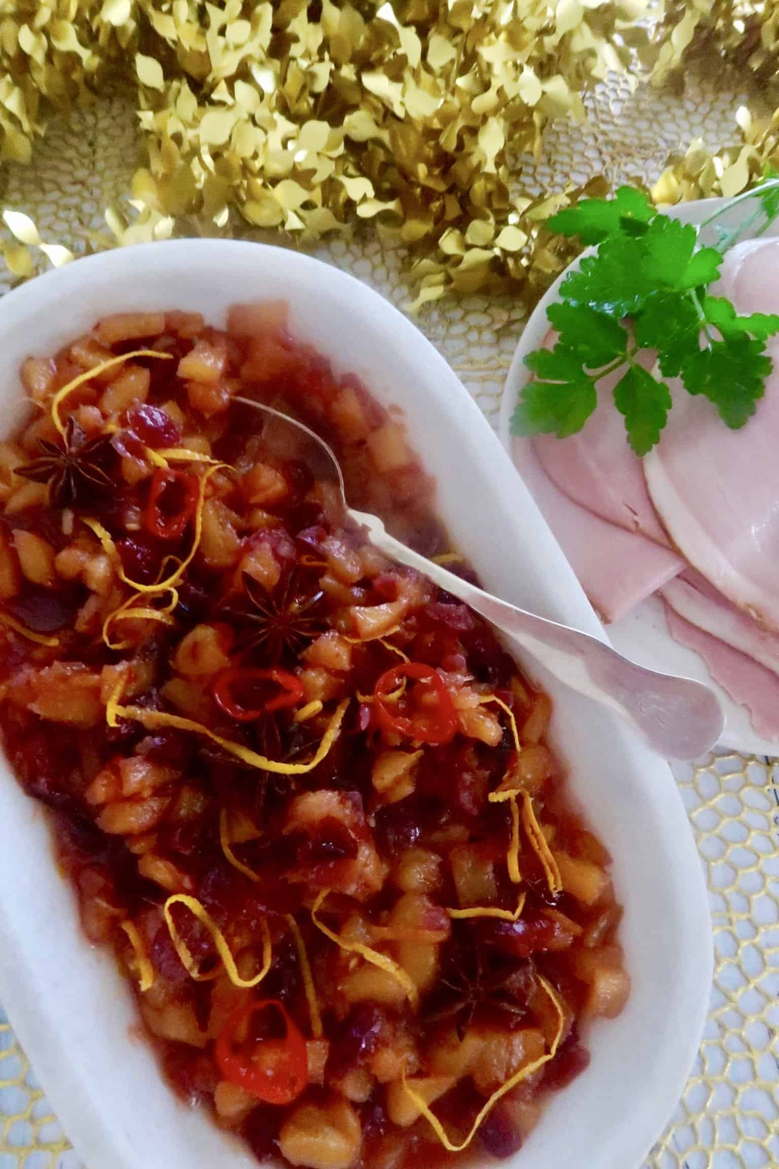 spicy pineapple and cranberry relish served in a oval marble bowl with ham in the background