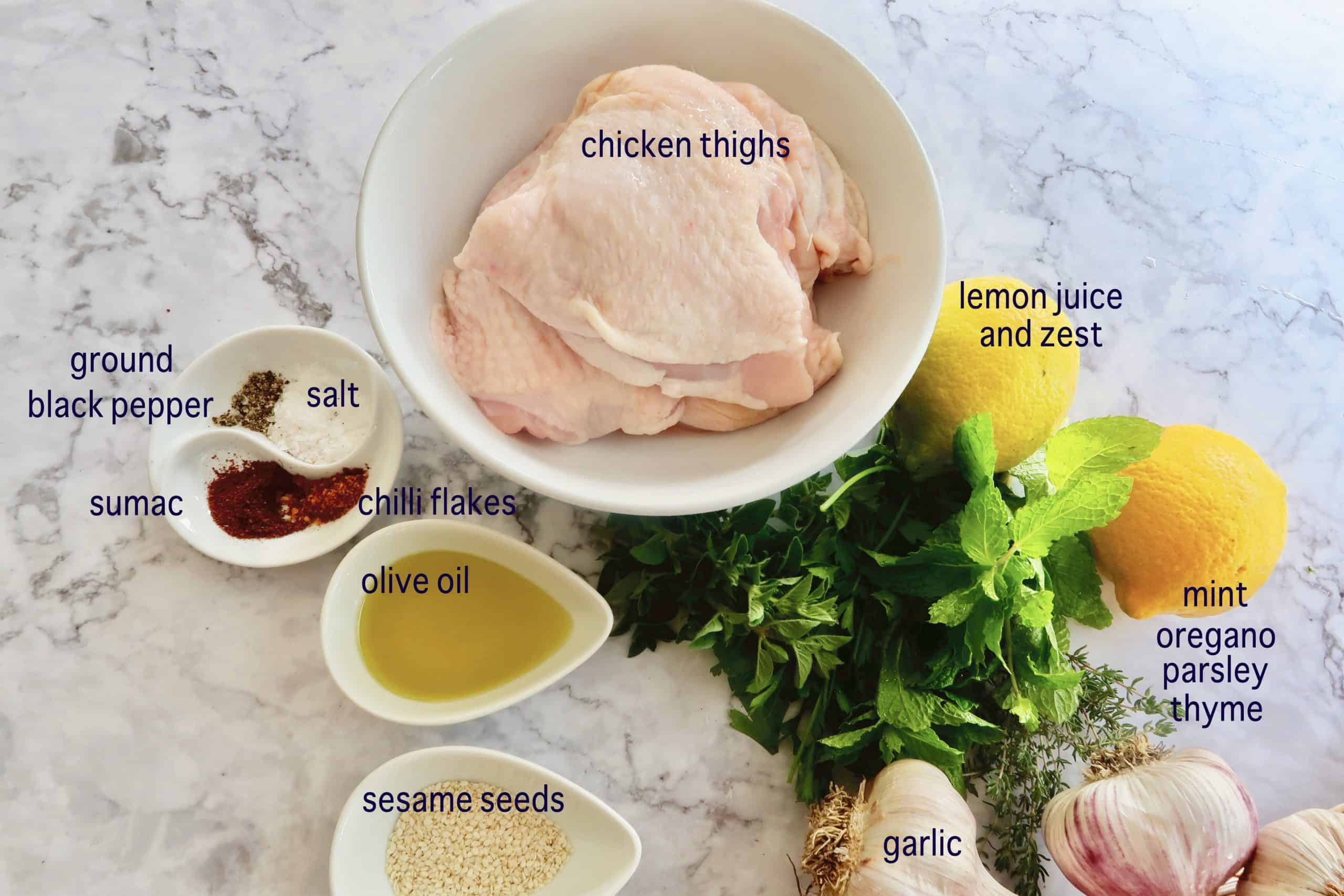 a marble table layed with the ingredients to makeMiddle Eastern Herb and Garlic Chicken Thighs