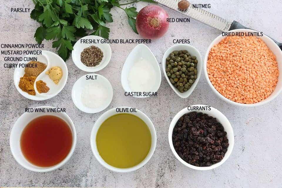 ingredients to make Spicy Red Lentils with Capers and Currants on a concrete table