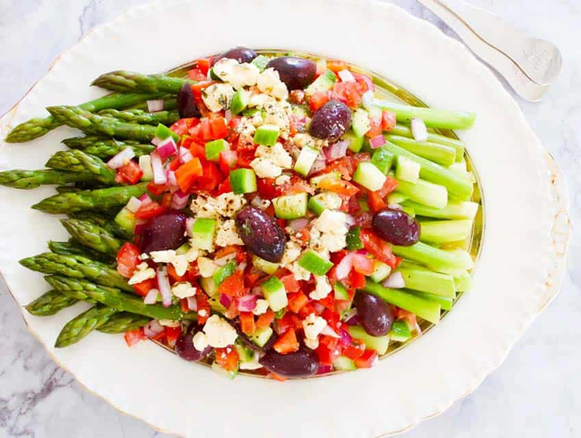 asparagus with greek salad medley served on a white and gold oval plate with a spoon and fork for serving