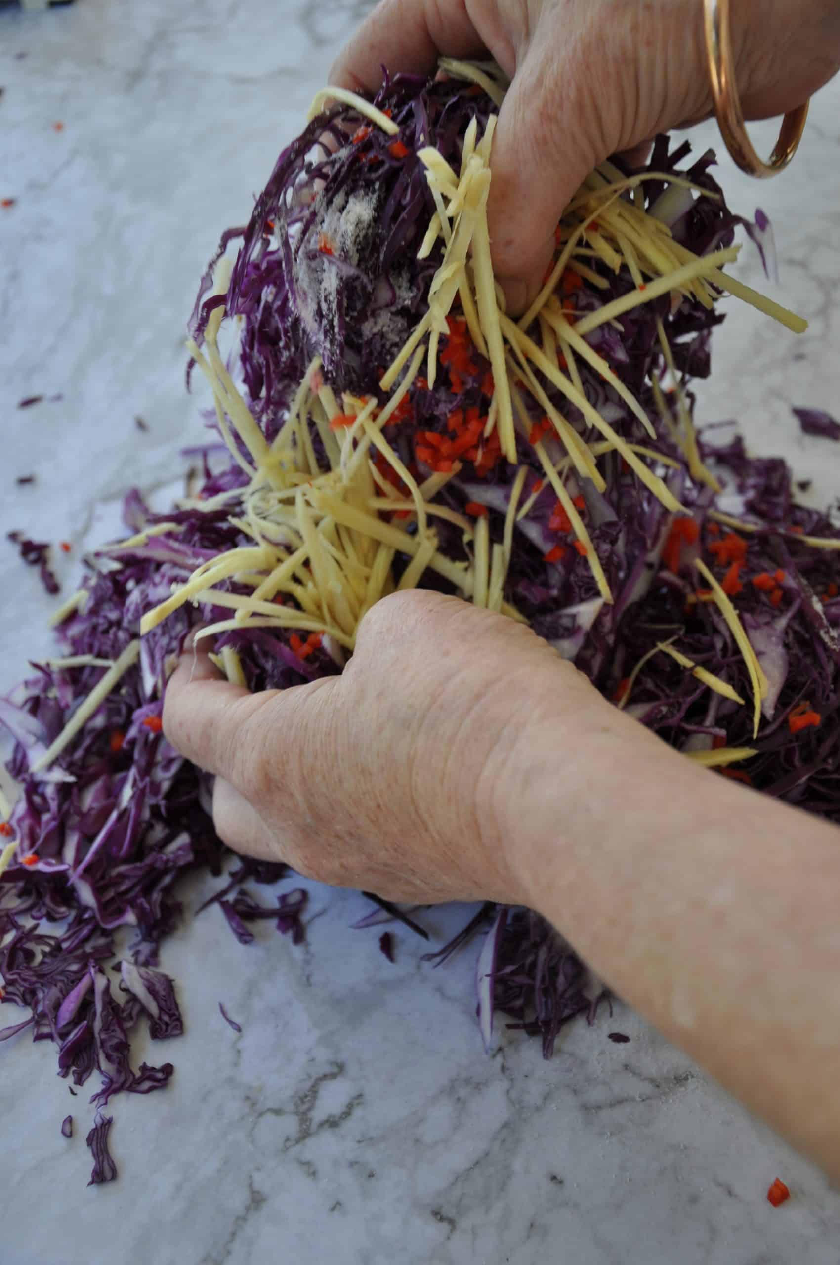 chinese pickled red cabbage with ginger tossing the ginger and chilli through the cabbage