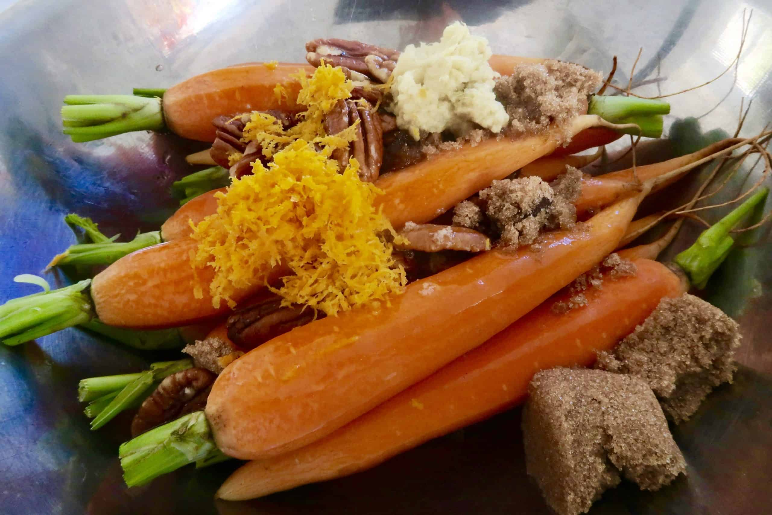 brown sugar and ginger glazed carrots with orange zest, brown sugar, ginger and pecan nuts ready to be tossed in butter