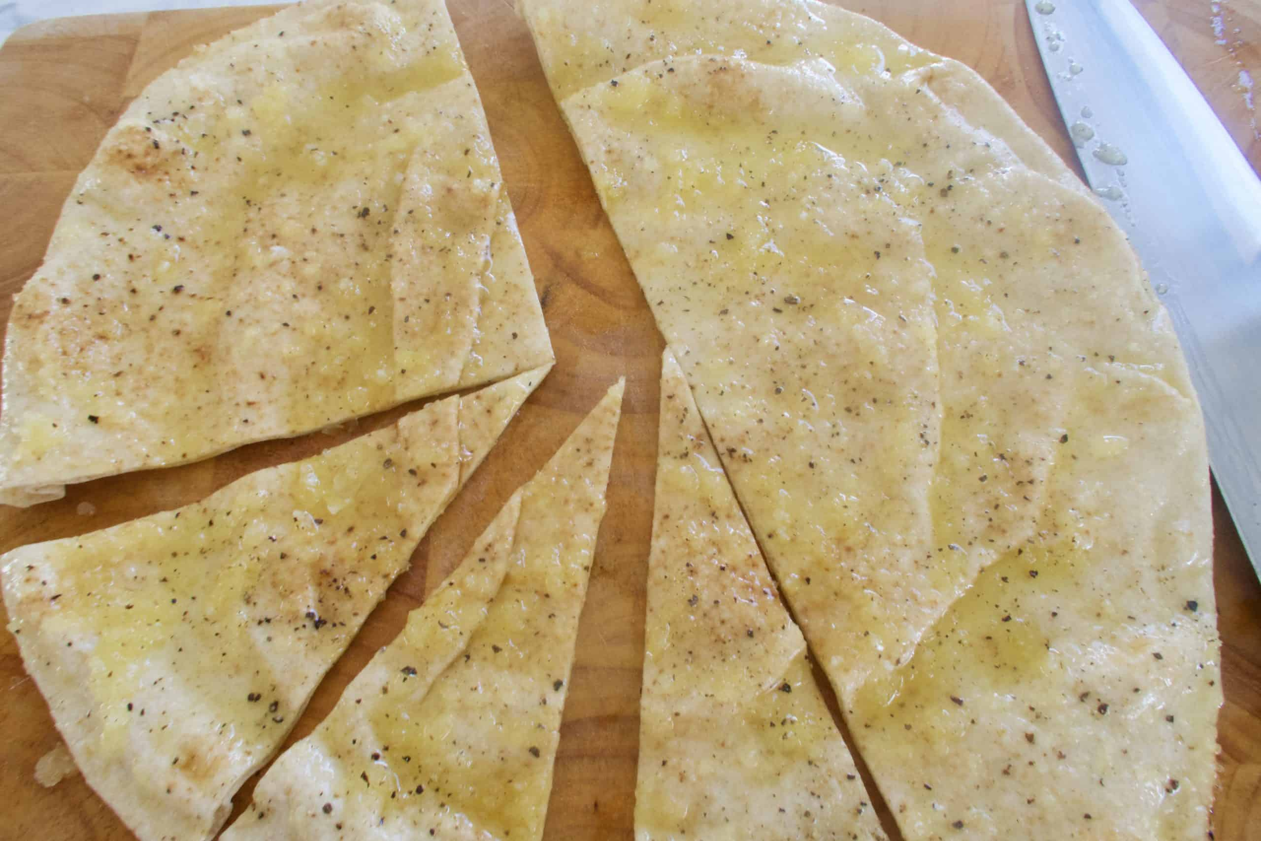 homemade baked pita chips with pita brushed with fresh minced garlic and oil