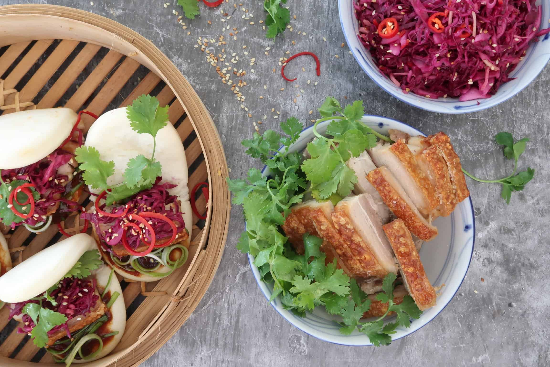 Chinese Pickled Red Cabbage served in bao buns in a bmboo steamer basket and a bowl of crispy porkbelly