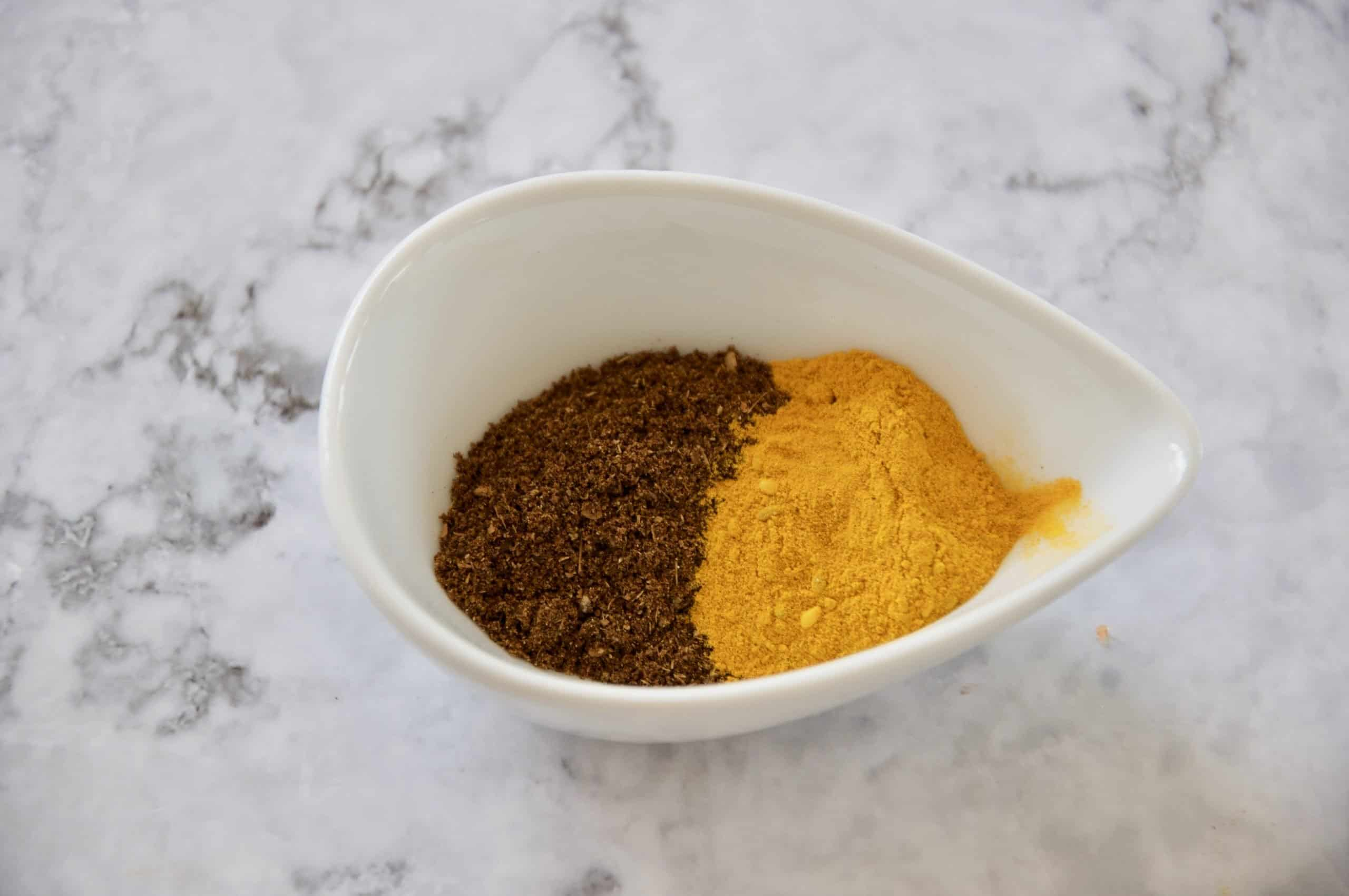 ground spices and turmeric at the opposite end in a white bowl to make Roasted Cauliflower Salad with Garlic Yoghurt Dressing