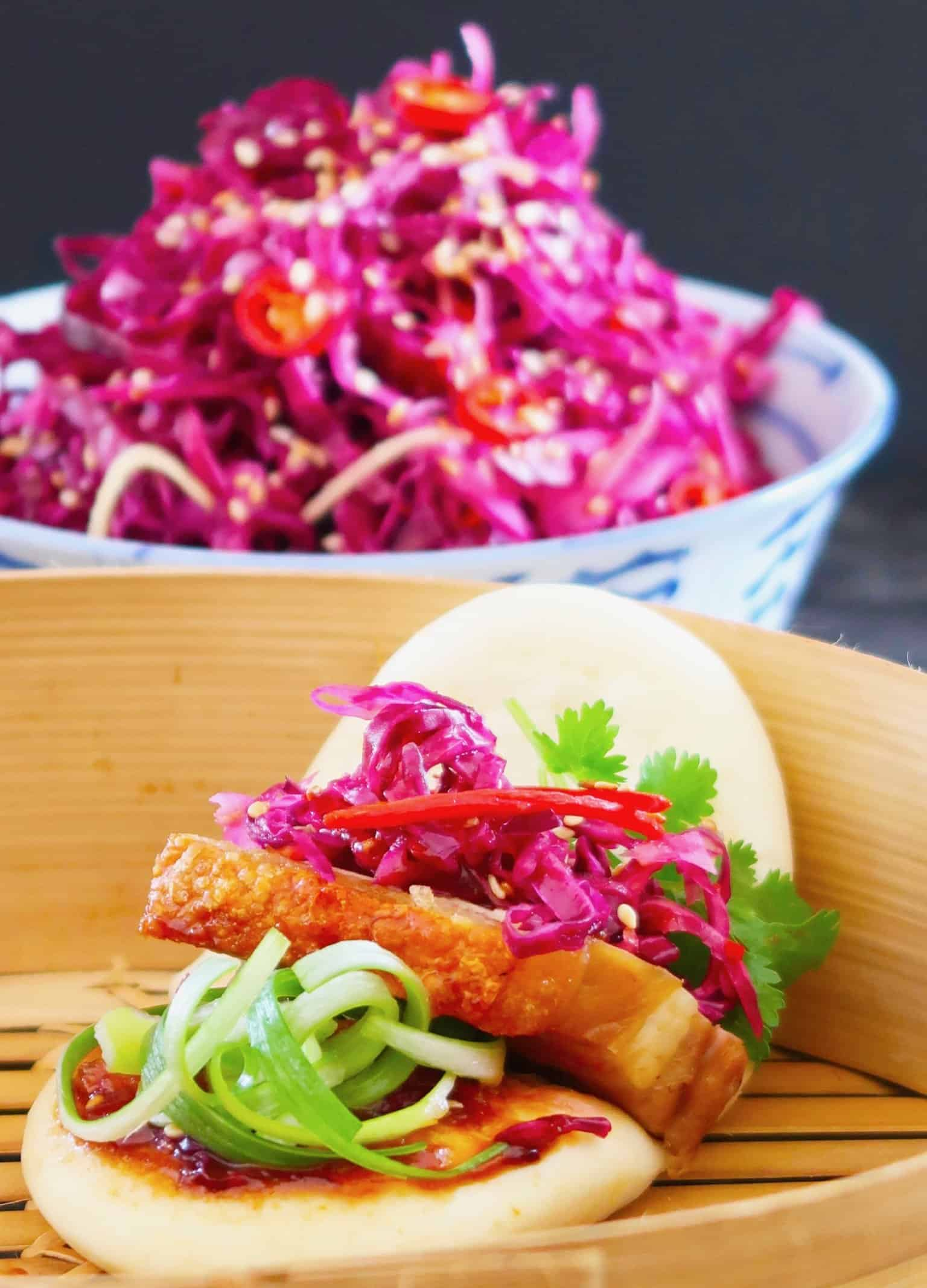 Chinese crispy pork belly slice served in a bao bun with red pickled cabbage