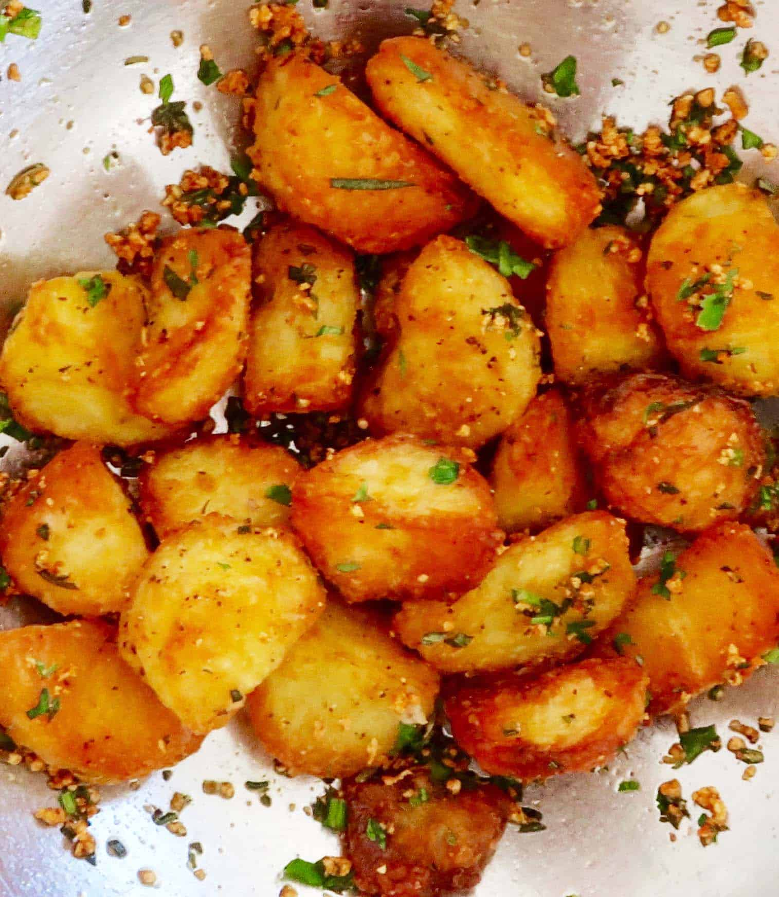 crispy roast potatoes in a metal bowl with parsley