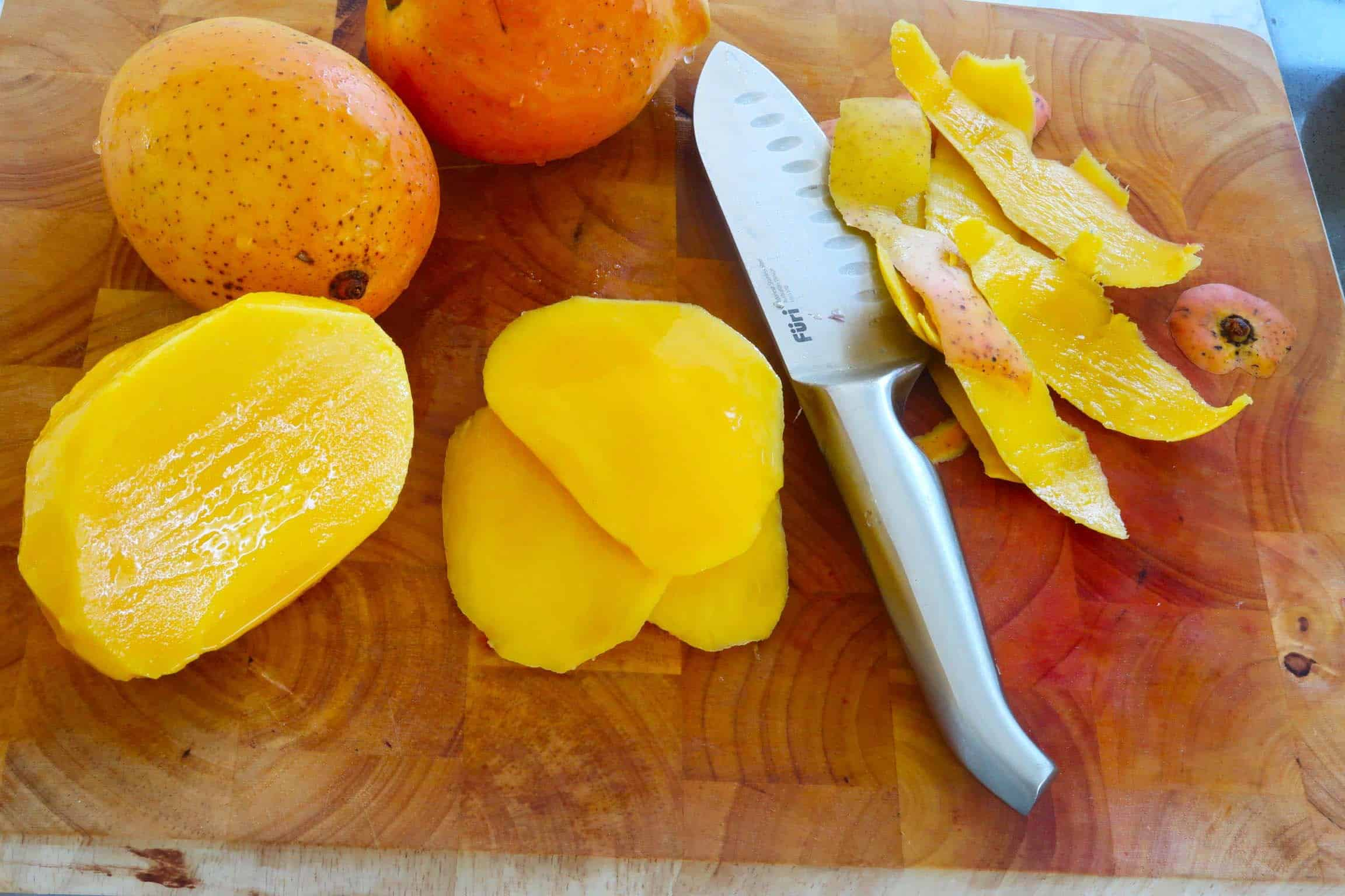 mango and red onion salad slicing and peeling mangoes on a wooden chopping board with a knife