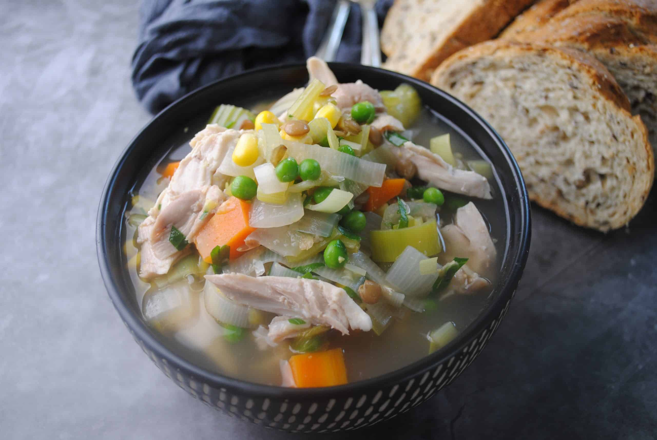 hearty chicken, vegetable and lentil soup ready to eat served in a dark bowl with crusty bread