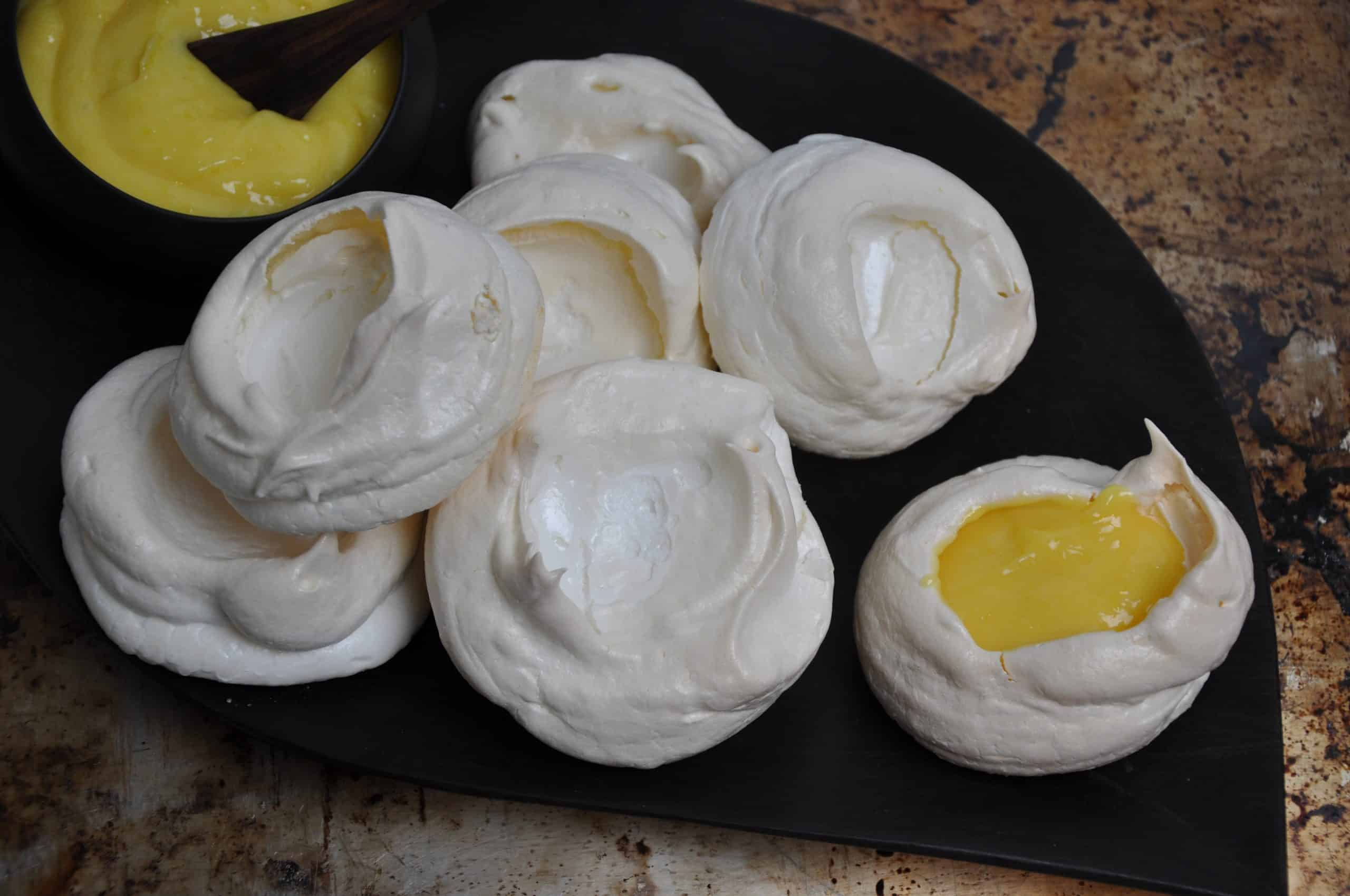 Meringues filled with lemon curd on a brown plate with a bowl of curd for serving