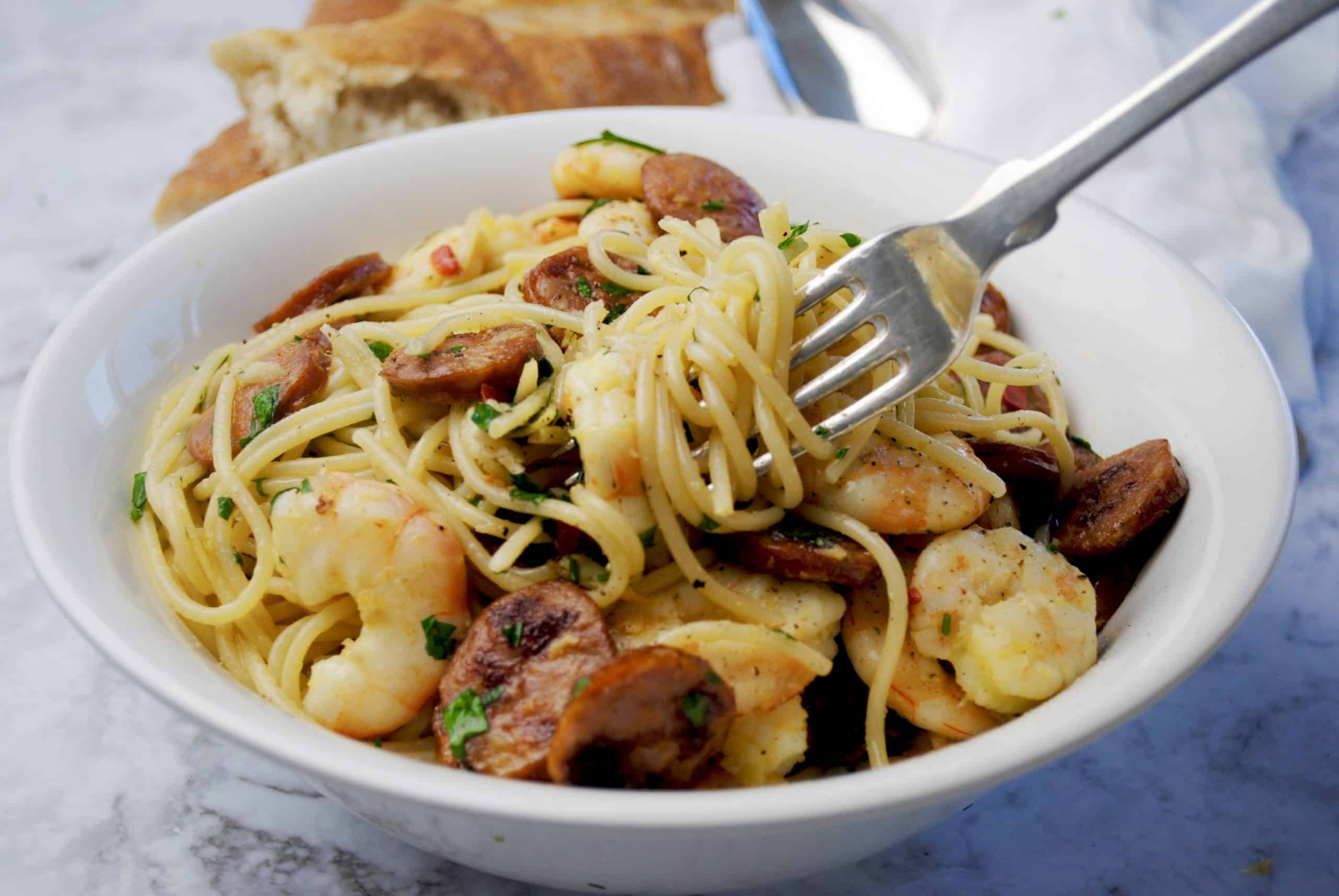 Chorizo & Prawn Pasta - Quick Spicy in white bowl with pasta twirled around a silver fork