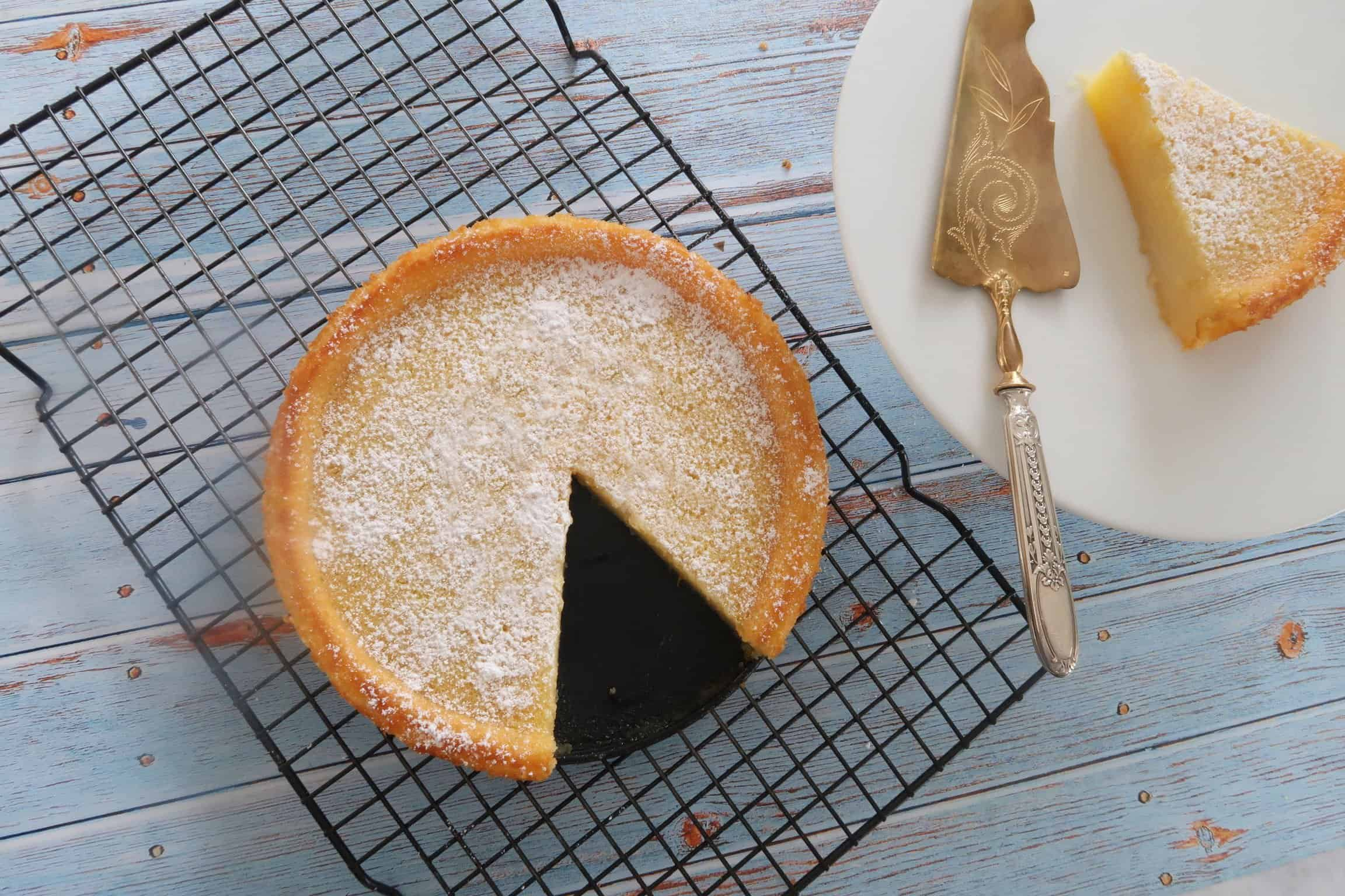 easy crustless lemon tart with a slice cut and served on a white plate with a cake server