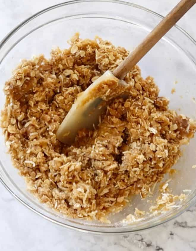 Anzac biscuit mixture mixed in a glass bowl ready to scoop out and bake