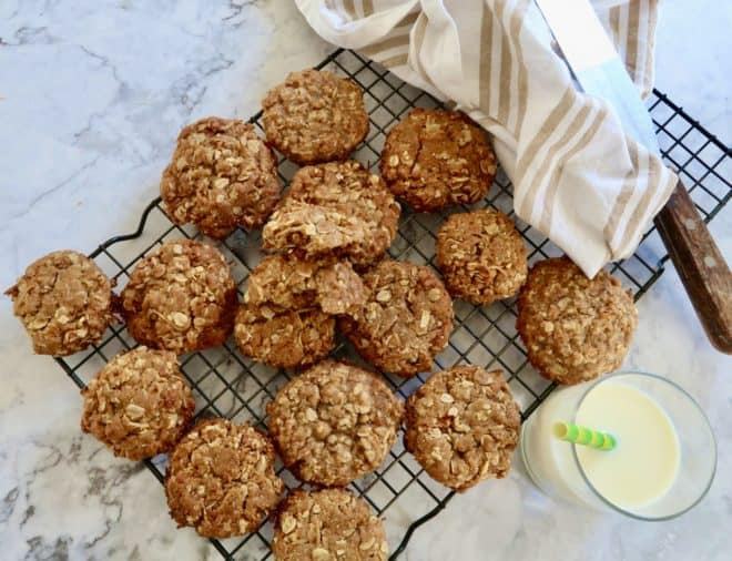 Anzac biscuits cooked and served on a cake rack with a glass if milk and a tea towel and spatula along with a small glass of milk with a green striped straw