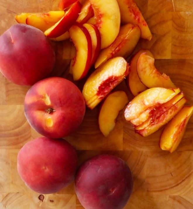 peach frangipane tart peaches on a wooden chopping board sliced and unsliced