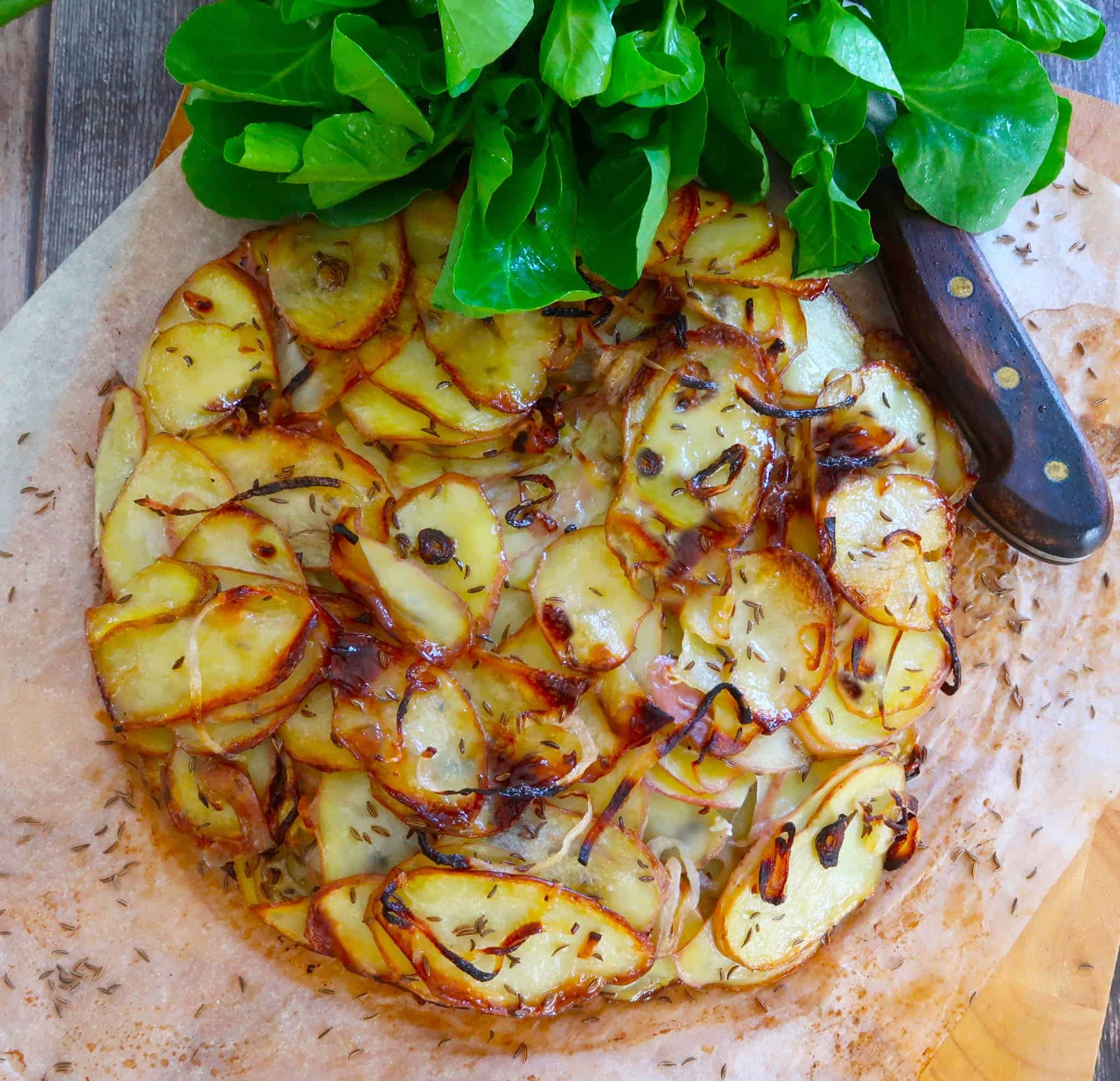 potato galette with duck fat and caraway on baking paper with a knife and watercress