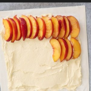 peach frangipane tart pastry with a 1 inch border covered with frangipane and peach slices added on top