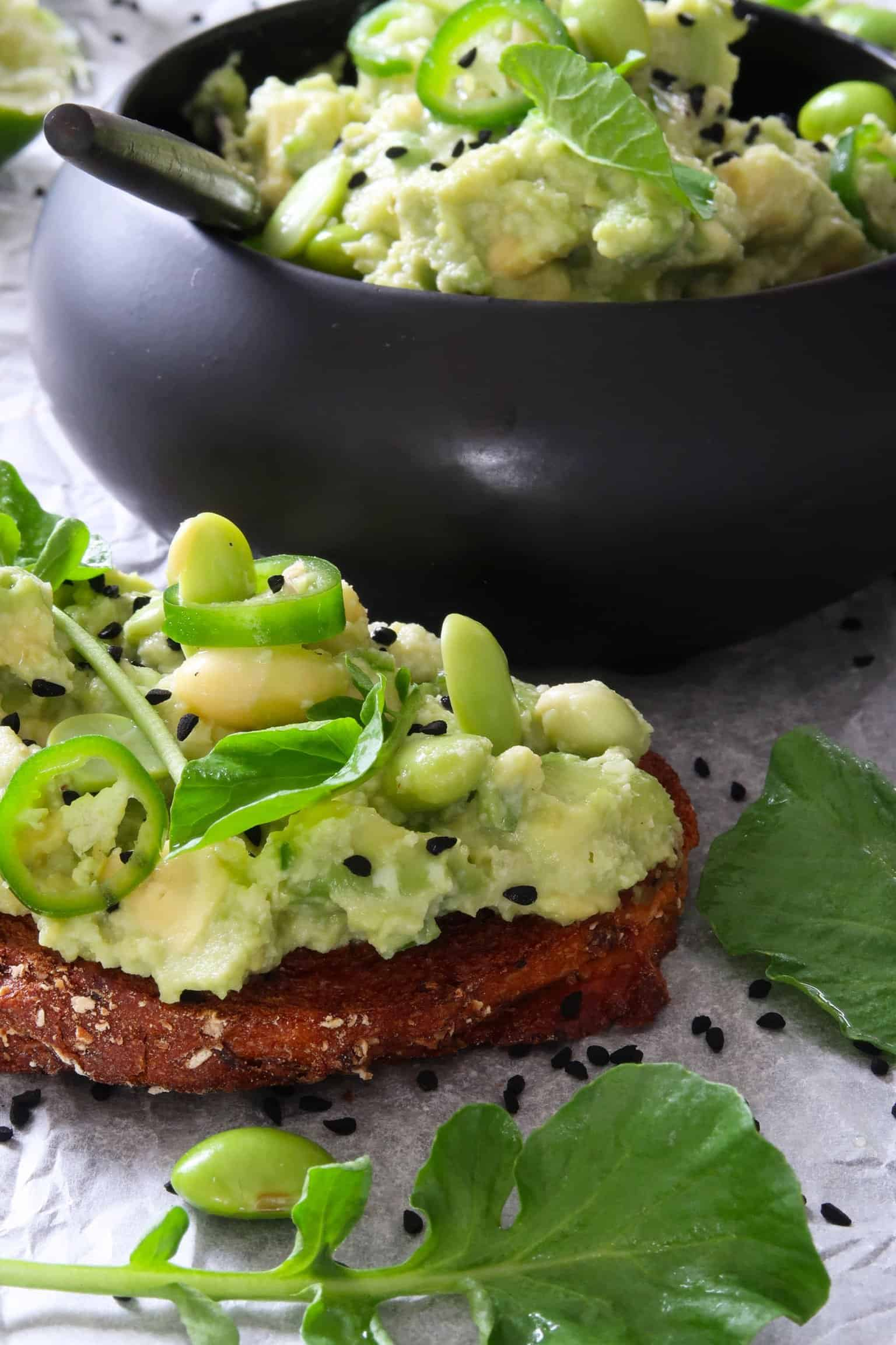 avocado and edamame smash served on toast with a bowl of smash behind it