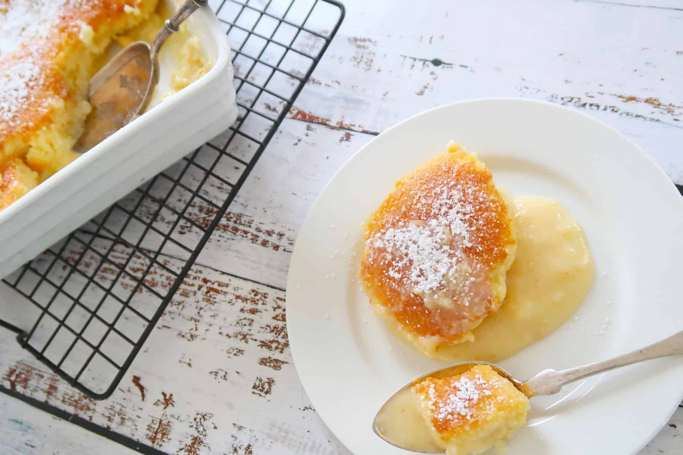 Lemon Delicious Pudding on a white timber board with a side plate and a spoon
