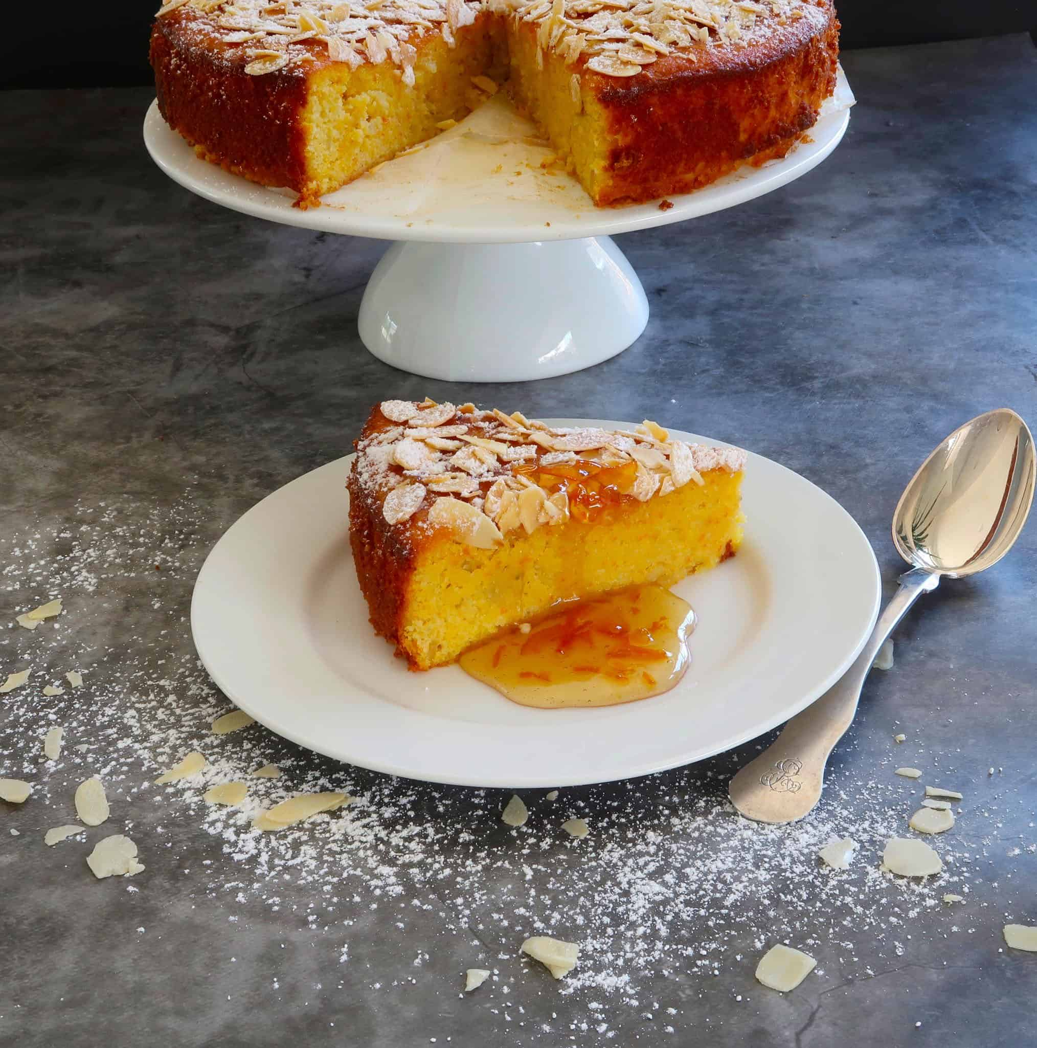 orange and almond cake with a slice served on a white plate and the cake in the background on a cake stand