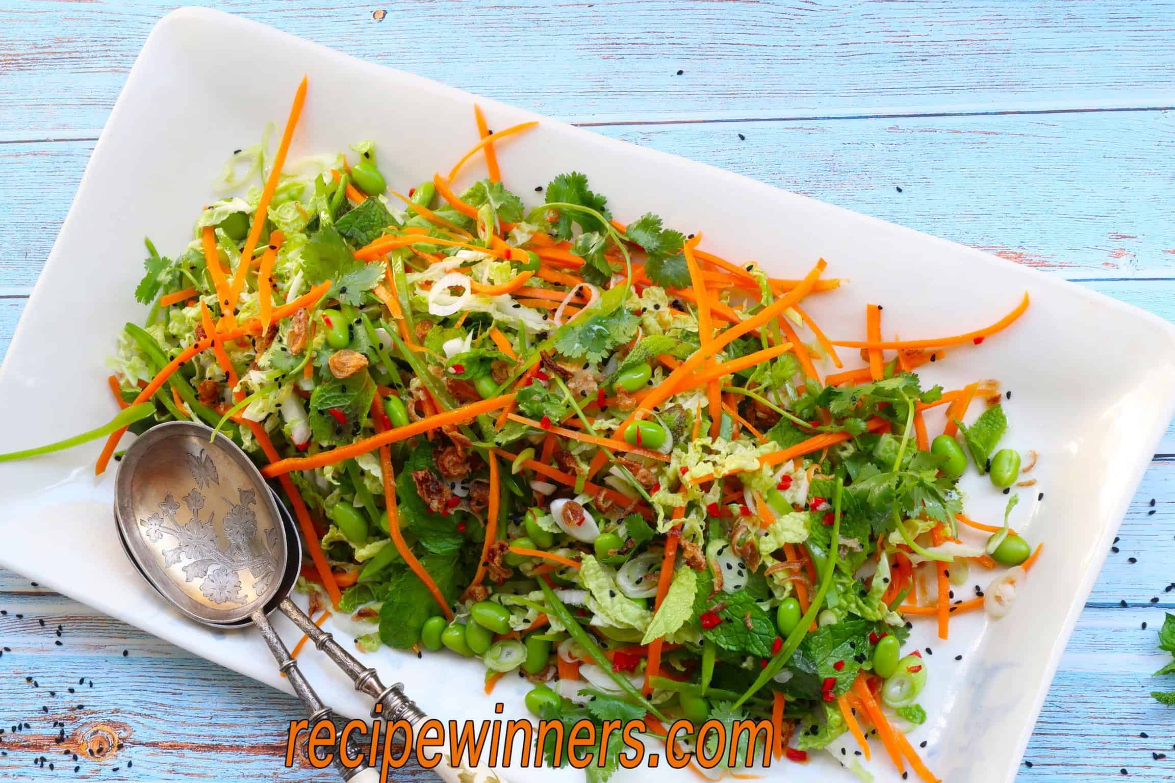 Asian slaw served on a white rectangular platter with two serving spoons