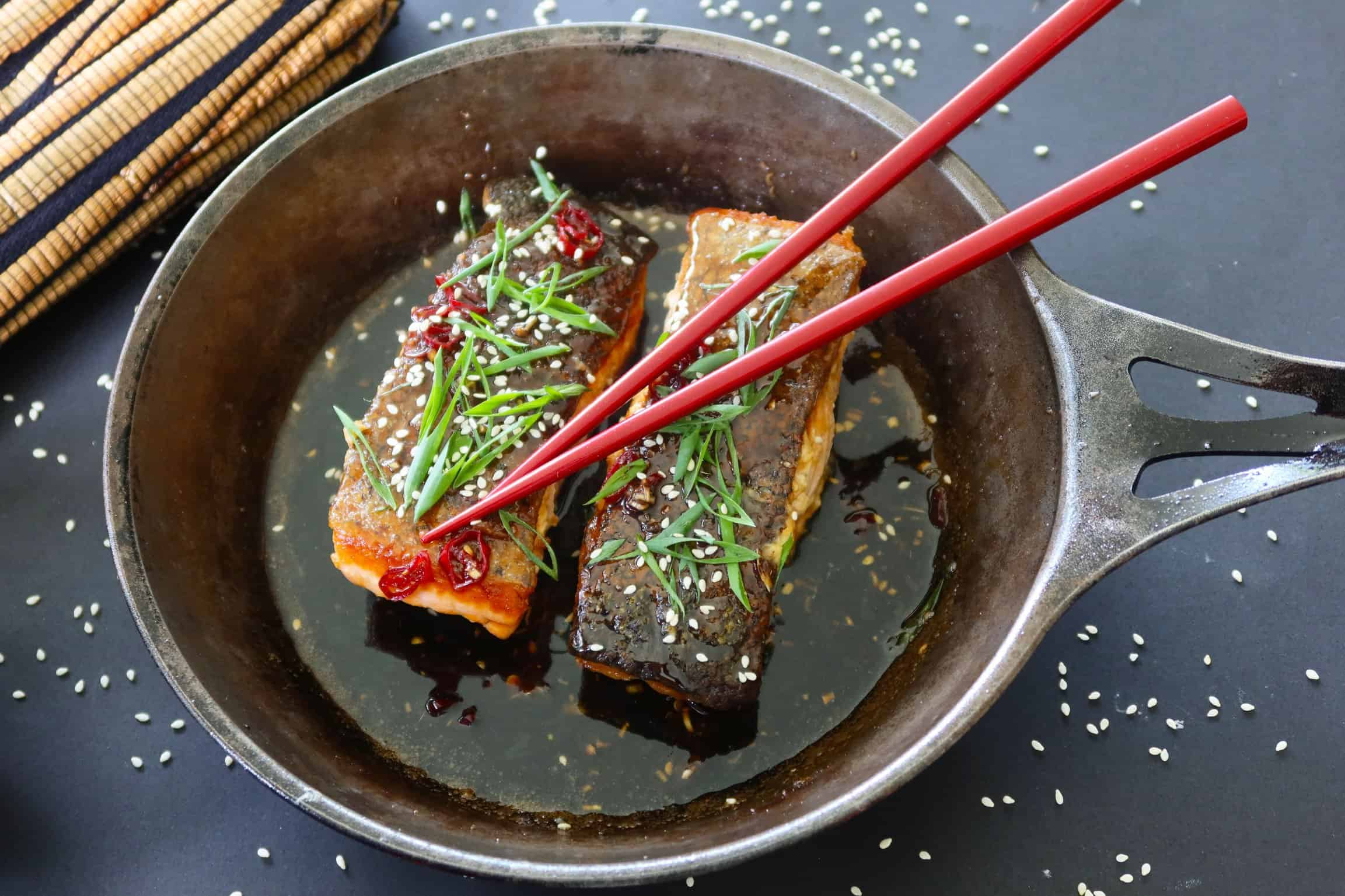 crispy skinned chilli caramel salmon ready to serve in a cast iron frypan with red chopsticks