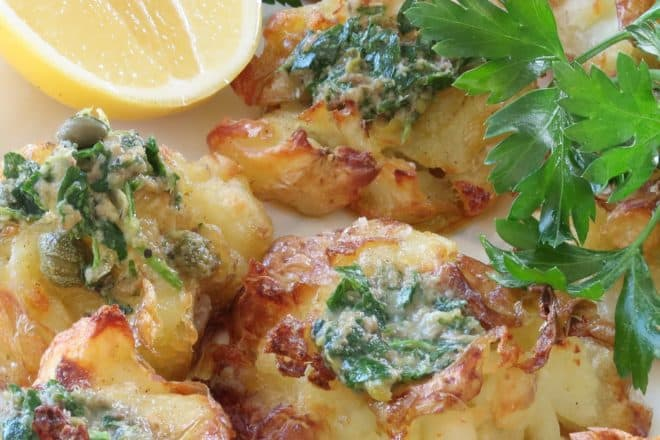 crispy roast potatoes with roasted garlic and caper dressing ready to serve