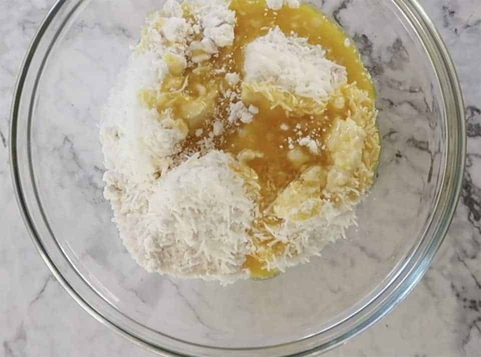 butter and coconut added to dry cake mix in a glass bowl while making apple and sour cream slice