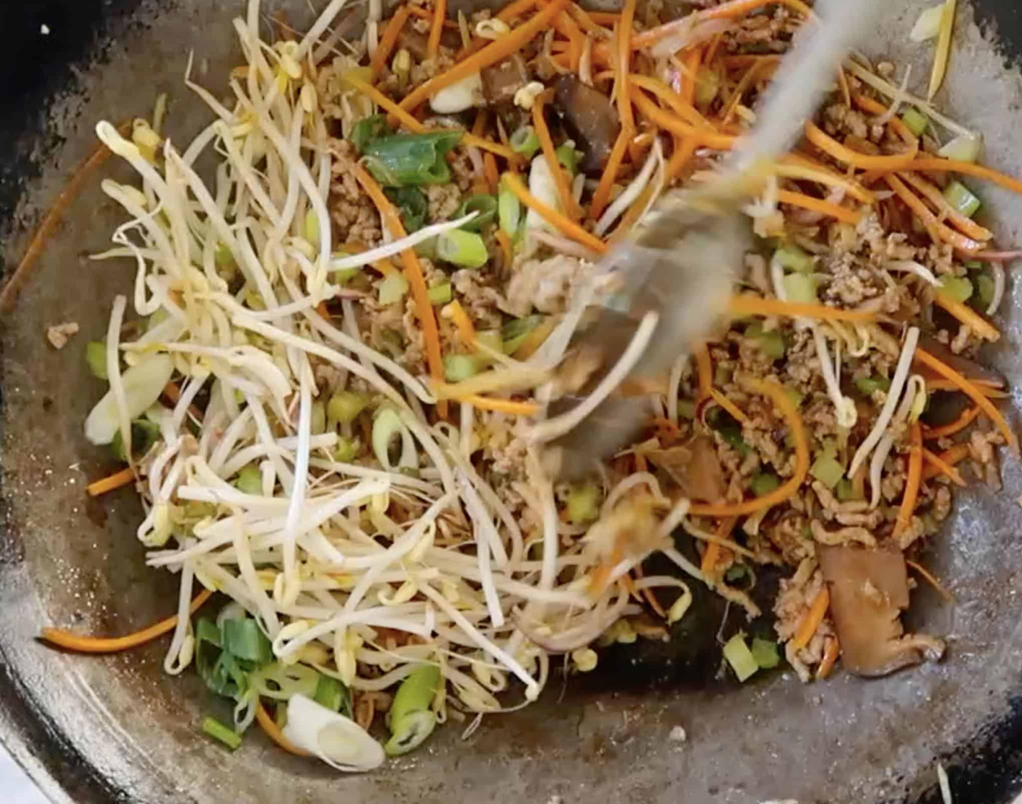 San Chow Bow adding bean sprouts to mix