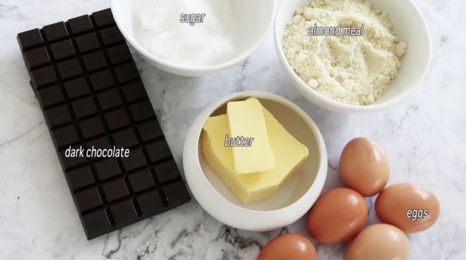 ingredients for chocolate almond cake in white bowls on a marble table