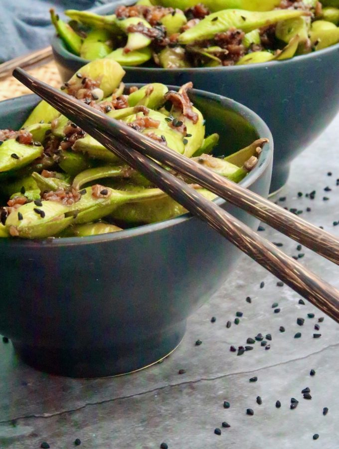 garlic chilli edamame served in a black bowl with chopsticks