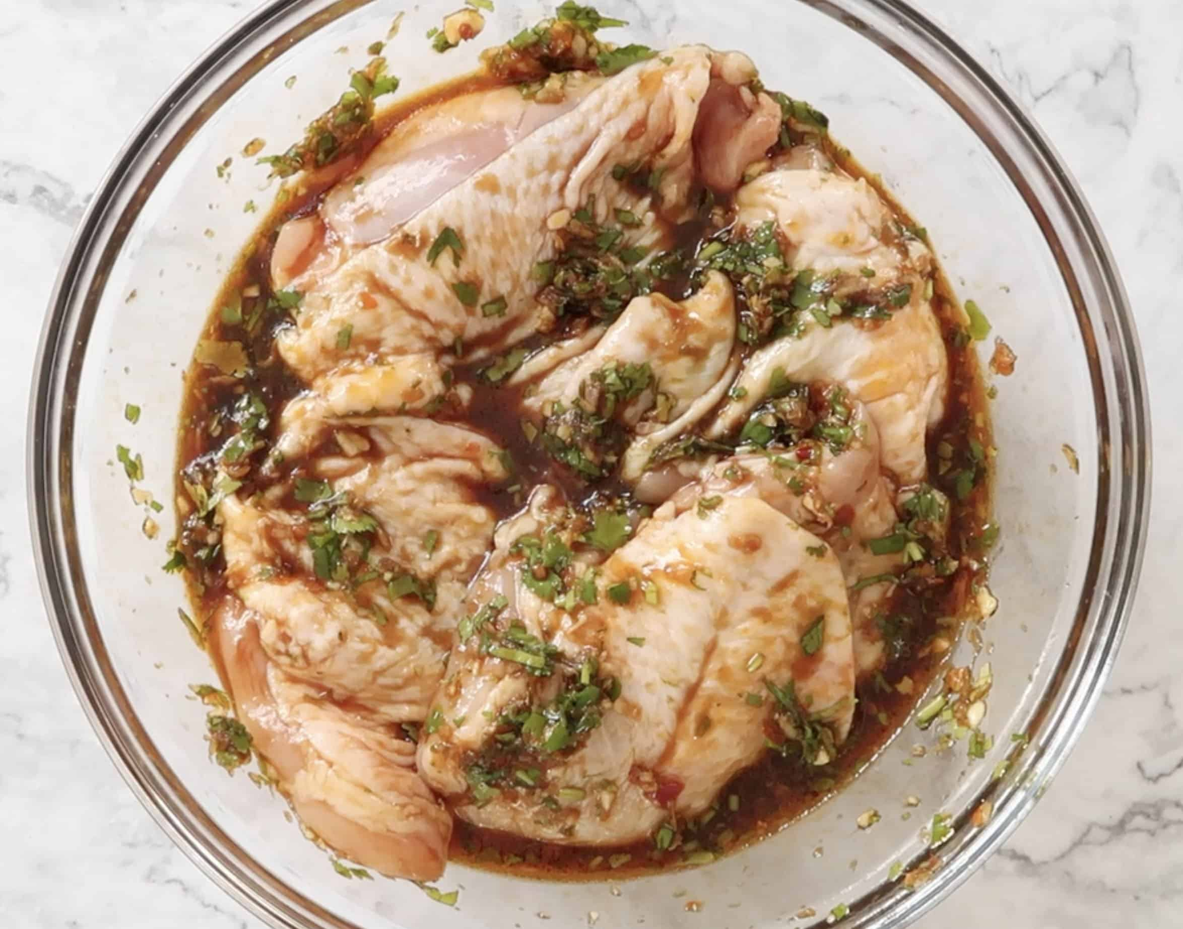 chicken thighs marinated in a glass bowl to make Vietnamese baked chicken thighs
