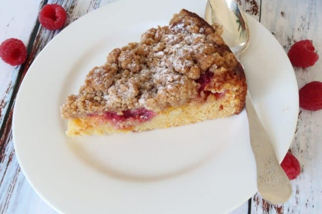 peach and raspberry streusel cake slice served on a white plate with a spoon