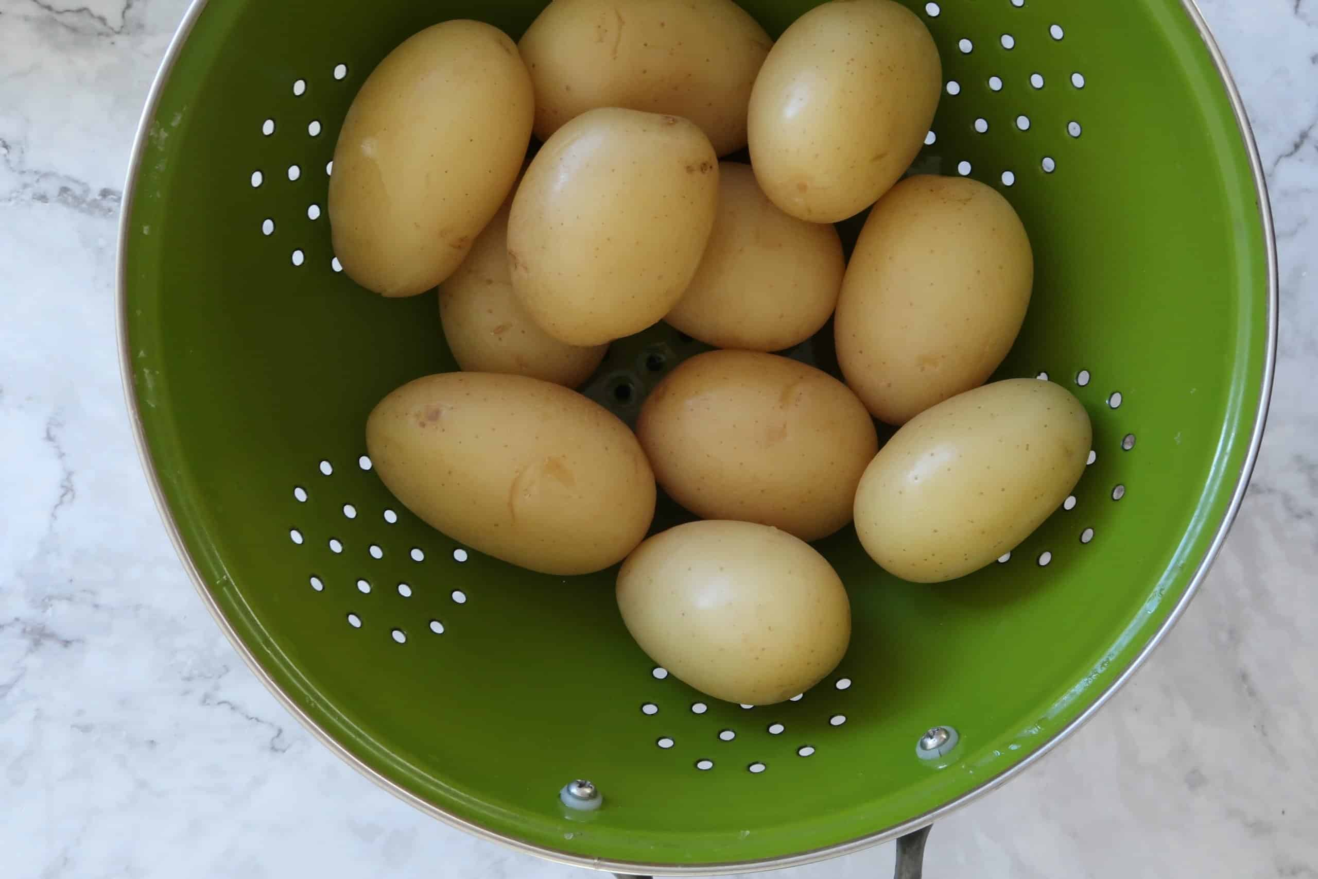 crispy smashed potatoes boiled and strained in a green colander ready to smash