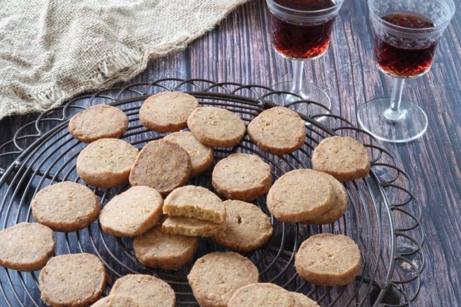 Anchovy, Cheese and Pine Nut Biscuits on a wire rack with two glasses of wine