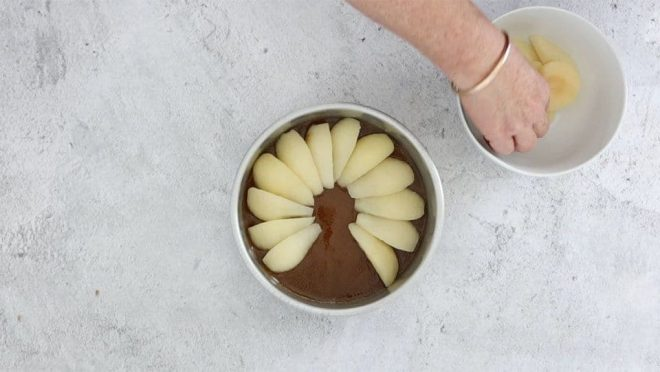 arranging the pears on the caramel pear and ginger upside down cake placing the sliced pers over the armel in the base of the cake tin