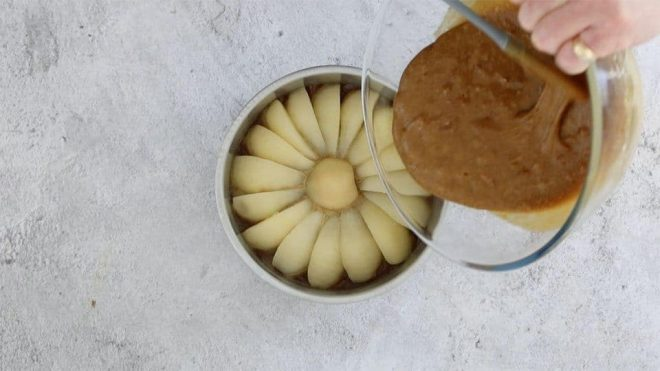 pouring the gingerbread batter over the pears in a cake tin to make easy pear and ginger upside down cake