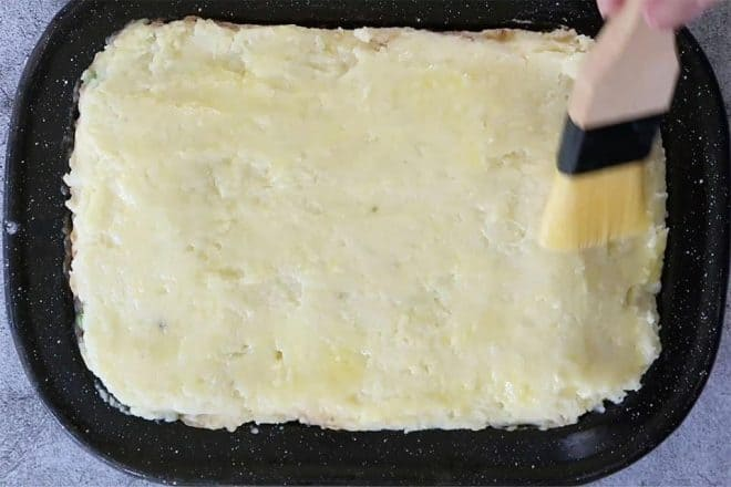 painting potato with butter forCottage Pie with Cauliflower Cheese Mash