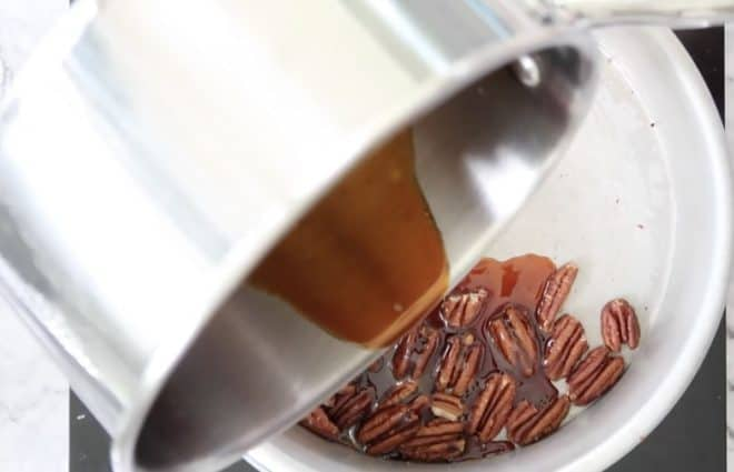 adding caramelised sugar to toasted nuts to make praline for salted caramel panna cotta with praline