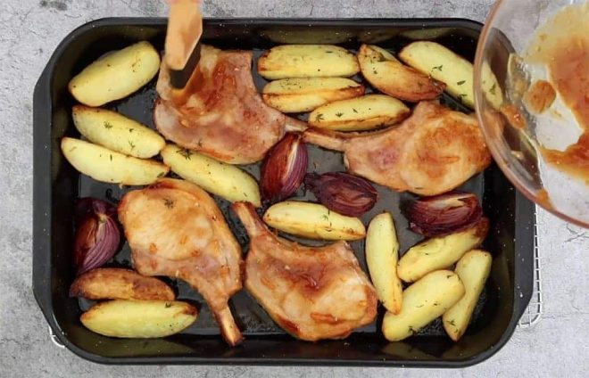 traybake pork chops with potatoes basting the chops with a marinade
