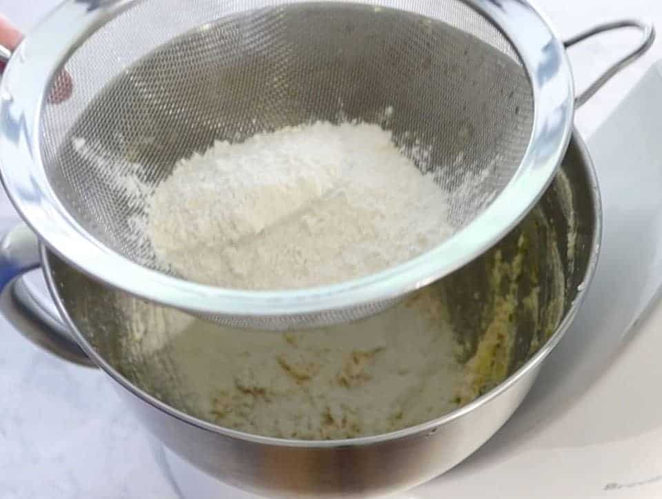 sifting flour into a mixing bowl to make lemon lava cakes