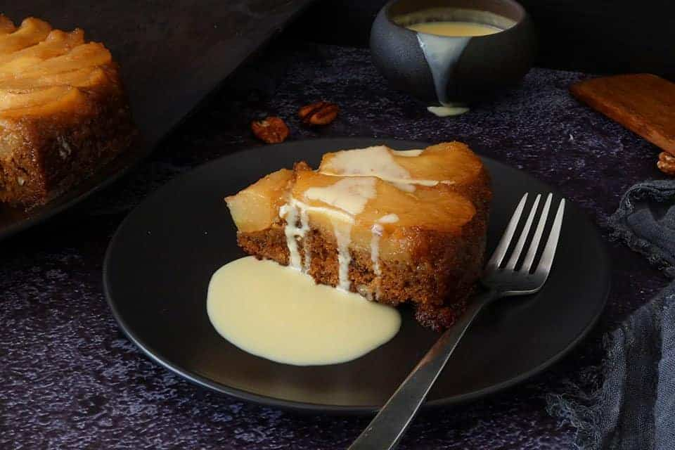 pear and ginger upside down cake with creme anglaise poured over it to serve on a dark plate