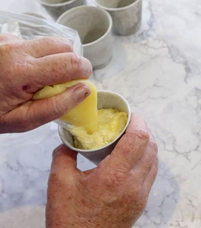 piping curd into batter for lemon lava cakes