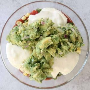 dollops of guacamole added to a glass bowl while making Mexican Layered Dip