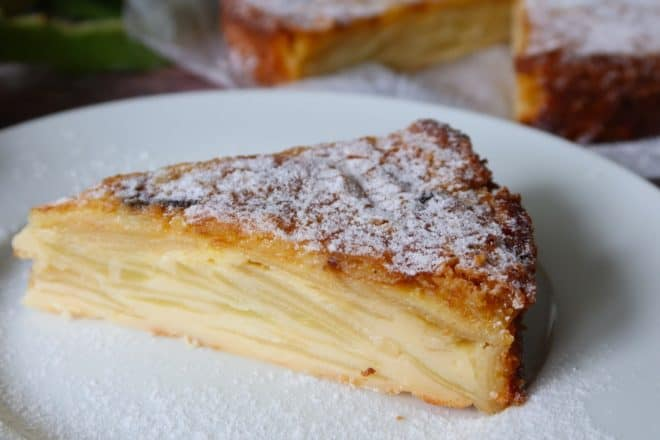 French apple cake slice served off a white plate